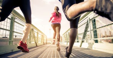 Drei Jogger rennen über eine Brücke.