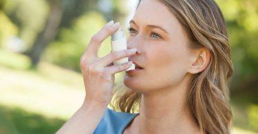 Foto einer jungen Frau, die einen Asthma-Inhalator verwendet
