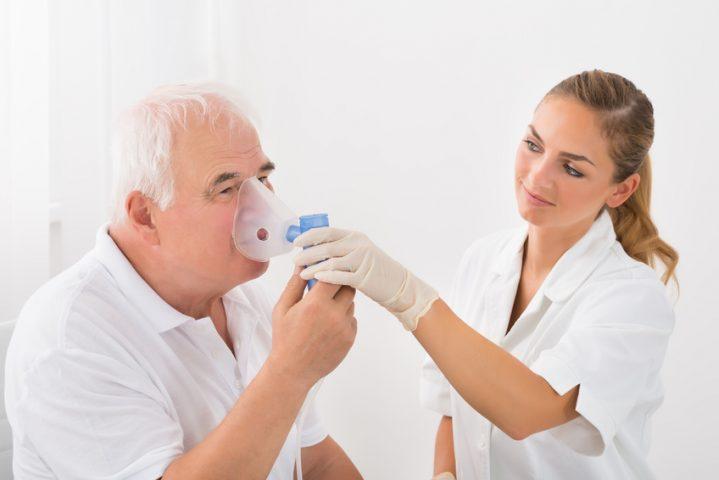 Foto eines COPD Patientenm der bei einer Reha den Umgang mit einer Sauerstoffmaske lernt
