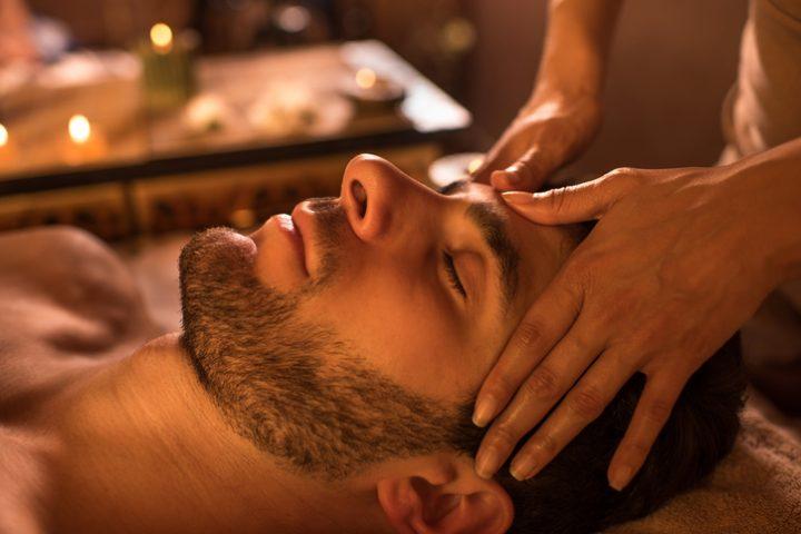 Foto: Entspannter Mann in der Kur bei einer Gesichtsmassage.
