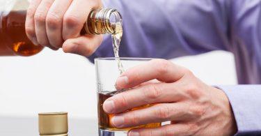 Foto eines Mannes mit Alkoholsucht, der sich Alkohol eingießt