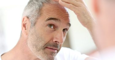 Foto: Mann kontrolliert seinen Haarausfall im Spiegel