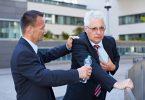 Foto: Geschäftmann hilft Senior mit Herzinfarkt mit einer Flasche Wasser