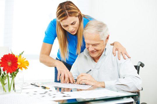 Pflegerin hilft Senior bei einem Kreuzworträtsel