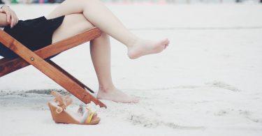 Eine Frau sitzt barfuß in einem Klappstuhl am Strand